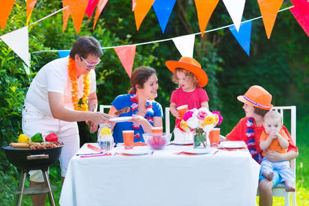 football party: Happy big Dutch family with kids celebrating a national holiday or sport victory having fun at a grill party in a garden decorated with flags of Netherlands, screaming Hup Holland Stock Photo