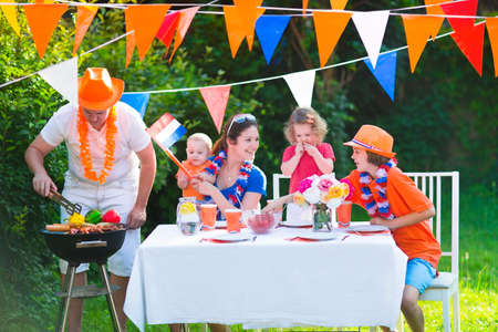 dutch girl: Happy big Dutch family with kids celebrating a national holiday or sport victory having fun at a grill party in a garden decorated with flags of Netherlands, screaming Hup Holland Stock Photo