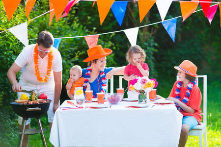 a big family: Happy big Dutch family with kids celebrating a national holiday or sport victory having fun at a grill party in a garden decorated with flags of Netherlands, screaming Hup Holland Stock Photo