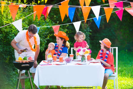Happy big Dutch family with kids celebrating a national holiday or sport victory having fun at a grill party in a garden decorated with flags of Netherlands, screaming Hup Holland Stock Photo