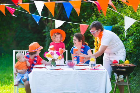 big family: Happy big Dutch family with kids celebrating a national holiday or sport victory having fun at a grill party in a garden decorated with flags of Netherlands, screaming Hup Holland Stock Photo