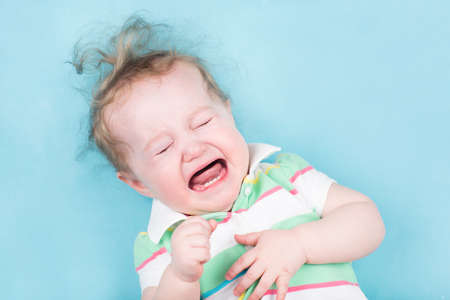 crying child: Sweet crying baby on a blue blanket