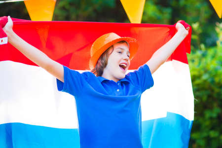 Happy Dutch boy, football fan, cheering and supporting soccer team of Netherlands during championship, celebrating sports victory screaming Hup Holland with national flag