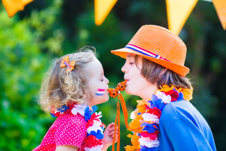 dutch girl: Two Dutch children, teenager boy and funny little girl, fans and supporters of Dutch football team, celebration championship victory playing with whistles decorated with flags Stock Photo