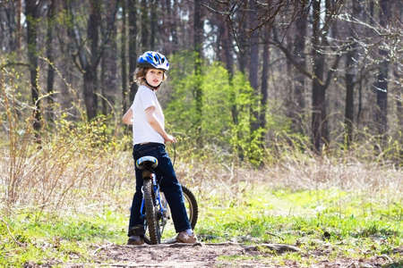 Young boy riding a bike in the forest  photo
