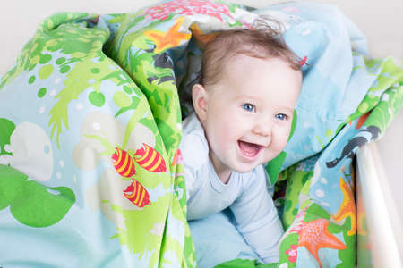 Funny baby playing in a bed under a blue blanket  photo