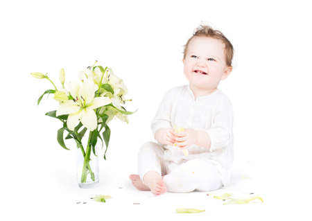 Funny little baby playing with lily flowers, on white  photo