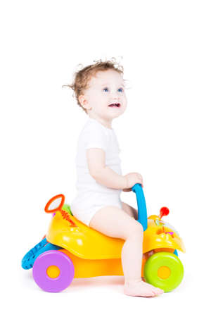 Cute baby with curly hair on a toy car  photo