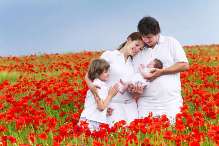 Beautiful young family with two children in a red flower field  photo