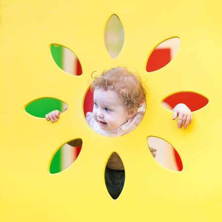 Funny curly baby girl playing hide and seek  photo