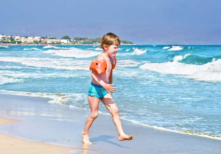 armbands: Little boy running on a beach wearing orange inflatable armbands  Stock Photo