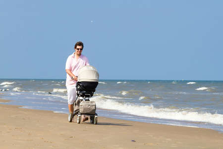 buggy: Young father walking with a stroller on a beach