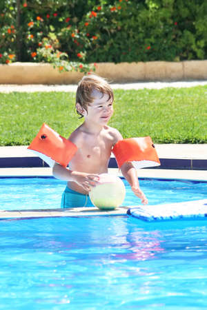 Little boy playing with a ball in a swimming pool  photo