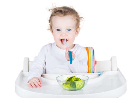 solid food: Sweet smiling baby eating broccoli, isolated on white