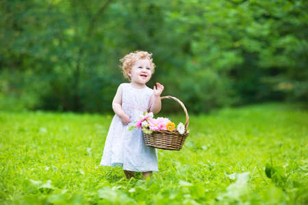egg hunt: Beautiful baby girl walking in a sunny garden with a flower basket