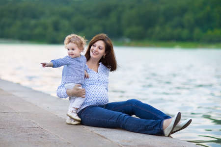 Young beautiful pregnant mother and her little baby daughter playing in a city center at a river bank  photo