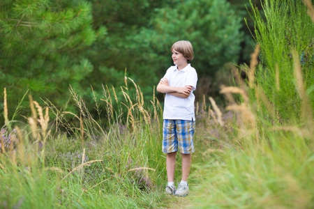 hide and seek: Cute school boy hiking in the woods in summer