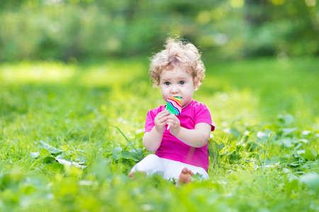 Adorable curly baby girl eating candy in a sunny summer park  photo