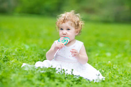 Beautiful baby girl with curly hair wearing a white dress eating candy in a park  photo