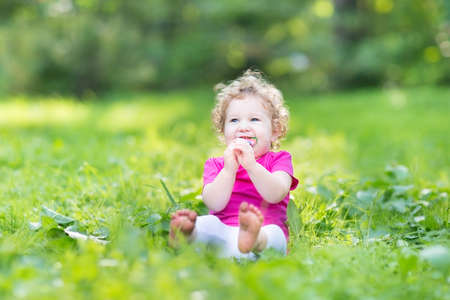 Adorable funny curly baby girl eating candy in a sunny park  photo