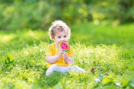 Cute curly baby girl eating water melon candy in a sunny park  photo