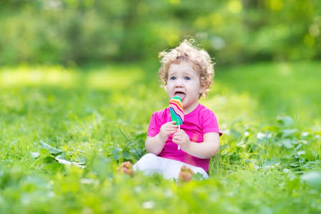 Beautiful curly baby girl eating candy in a sunny park  photo