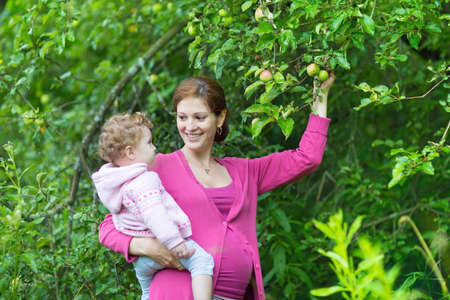 Happy young pregnant mother and her one year old baby daughter playing in a fruit garden under an apple tree  photo
