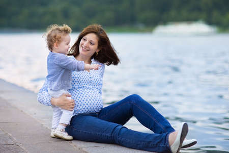 Young pregnant mother and her little baby daughter relaxing at a river bank in a city center  photo