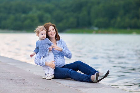 Young attractive pregnant mother and her adorable curly baby daughter playing at a river bank in a city center  photo