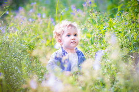 Adorable baby girl playing in a garden on a sunny summer day among beautiful blue flowers  photo