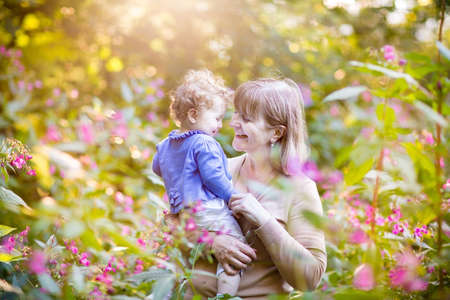 among: Beautiful woman playing with a happy baby girl in a garden at sunset among pink and red wild flowers
