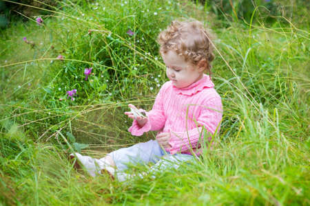 among: Adorable baby girl playing with a snail in the garden among beautiful wild flowers  Stock Photo