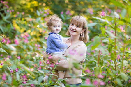 Young woman holding a baby girl in a garden on sunset among beautiful pink flowers  photo