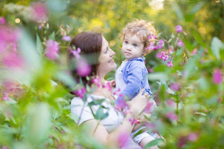 Beautiful young mother playing with her one year old baby daughter on a sunny summer evening in a garden with big pink and red flowers