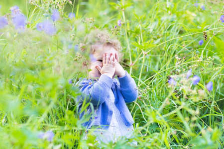 peek a boo: Cute funny baby girl playing hide and seek in the garden with blue and purple flowers  Stock Photo