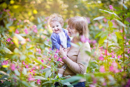 Beautiful woman playing with a laughing baby girl on sunset in a garden with pink and red flowers  photo