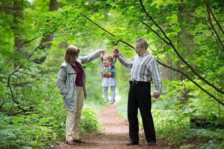 その赤ちゃんの孫娘で遊んで若い祖父母、秋、公園 写真素材