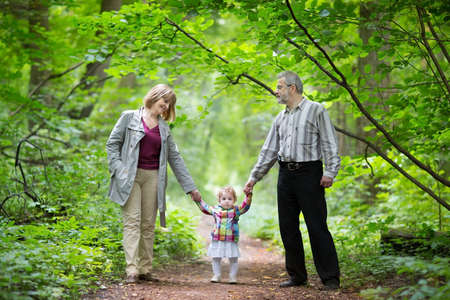 Young grandparents walking with their baby granddaughter in a park in autumn  Stock Photo