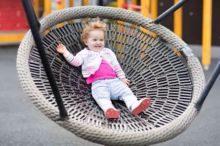 jungle gym: Happy laughing baby girl relaxing on a swing on a playground