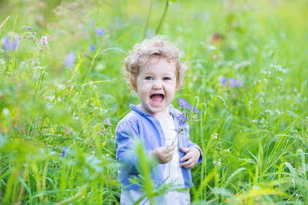 Adorable laughing baby girl playing with blue flowers in a garden on a sunny summer day  photo