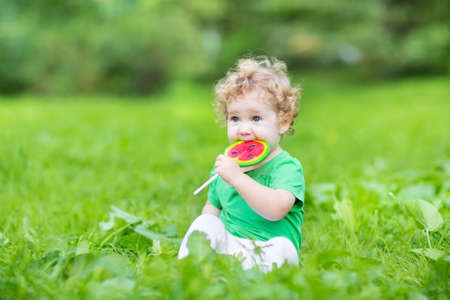 Beautiful curly baby girl eating watermelon candy in a summer park on a warm sunny day  photo
