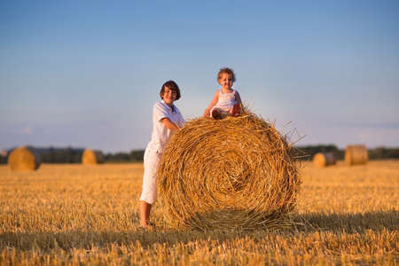 hay: Brother and baby sister playing in a field of hay bales at sunset