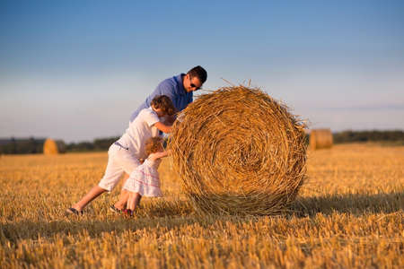 Young father and two children, a boy and a baby girl, playing in a hay bales field at sunset  photo