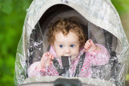 cover girls: Cute curly baby girl sitting in a stroller under a plastic rain cover on a cold and rainy autumn day  Stock Photo