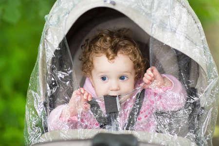 sotto la pioggia: Cute ragazza riccia bambino seduto in un passeggino sotto una copertura per la pioggia di plastica in un giorno di autunno freddo e piovoso Archivio Fotografico
