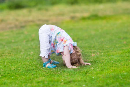 Adorable funny baby girl standing with her head down in a summer  photo