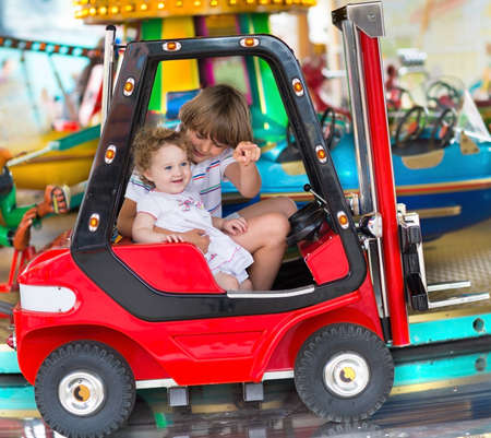 Brother and little baby sister enjoying a ride in an amusement park  photo