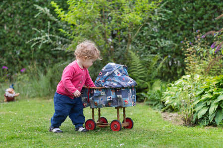 Adorable curly baby girl playing with a vintage toy stroller in the garden  photo