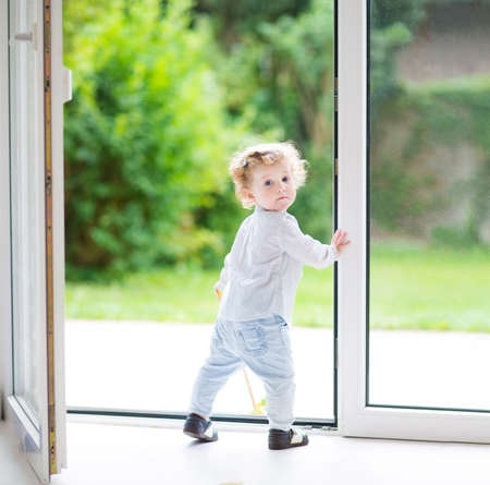 Adorable curly baby girl standing at a big glass door to the garden
