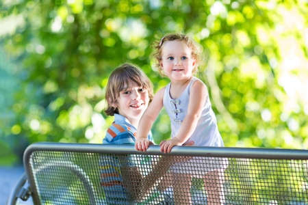 Adorable baby girl with curly hair wearing a blue dress playing with her brother sitting on a bench in a sunny summer park at a river shore  photo